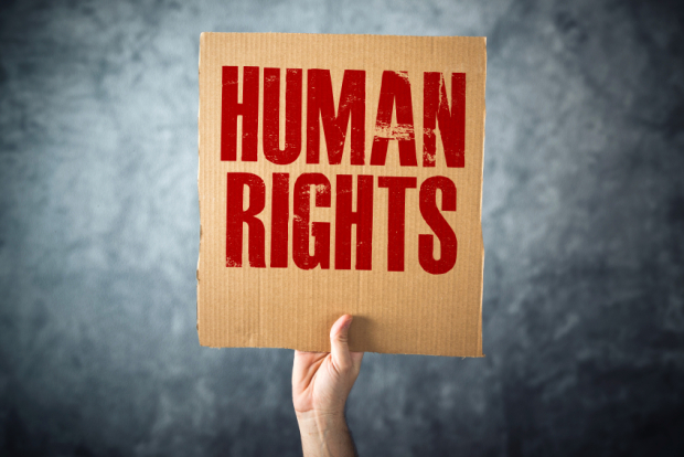 A hand holding up cardboard sign saying human rights