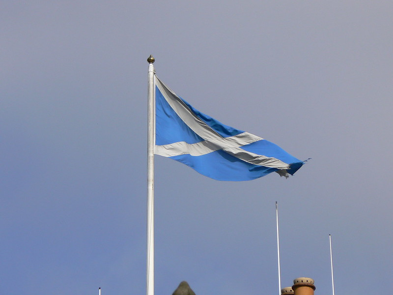 A flagpole with a Scotland Saltire flag blowing in the wind