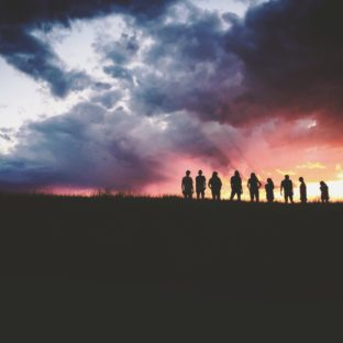 A group of people silhouetted against a sunset with clouds