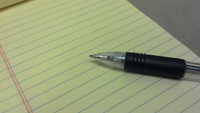 A black pen lying on lined paper