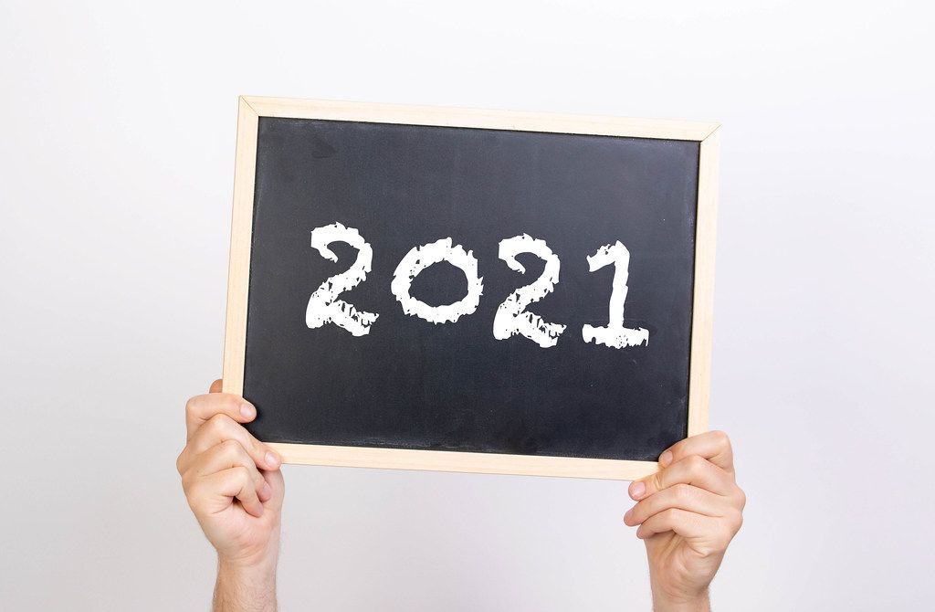 Hands holding up blackboard with date 2021